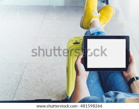 Young hipster girl at airport in yellow boot on suitcase waiting air flight, female hands holding computer in terminal departure lounge gate, traveler trip concept, mock up of blank screen tablet #481598266