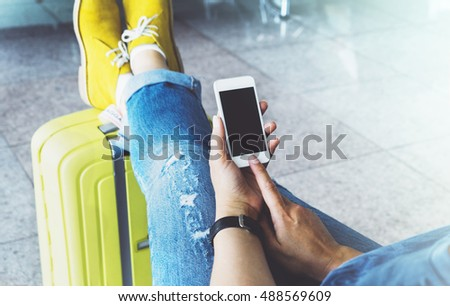 Young hipster girl at airport in yellow boot on suitcase waiting air flight, female hands holding smart phone in terminal departure lounge gate, traveler trip concept, mockup of blank screen sellphone