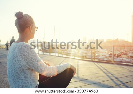 Young hipster girl enjoying sun and good warm day during her recreation time, woman relaxing outdoors after walking in the fresh air, female looking at the landscape while sitting near sea port  ストックフォト ©