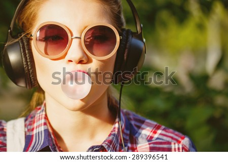 Young hipster girl listening to music on headphones in a summer park. Portrait close-up with chewing gum. Warm toning. Concept of cheerful youth. stock photo
