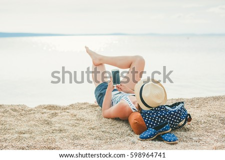 Young hipster girl texting in a smartphone on the beach with the sea in the background