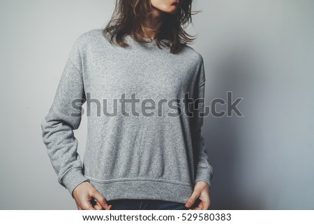 Young hipster girl wearing blank grey cotton sweatshirt with copy space for your design or logo, mock-up of grey template women'?s hoodie, white wall in the background