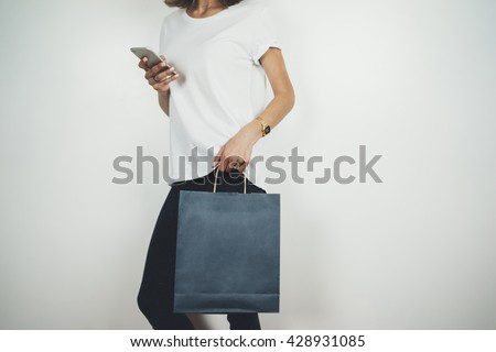 Young hipster girl wearing white t-shirt and holding blank blue shopping bag, mock-up of blue paper package, white background