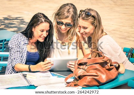 Young hipster girlfriends studying and having fun together with tablet - Social interaction on new technology trends and internet connection in everyday vintage lifestyle - Sunny day warm lighting