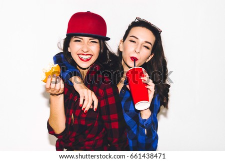 Young hipster girls having fun drinking a soda from straw and holding a burger, smile and laugh on the white background. #661438471