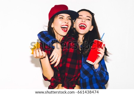 Young hipster girls having fun drinking a soda from straw and holding a burger, smile and laugh on the white background. #661438474