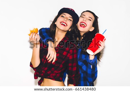 Young hipster girls having fun drinking a soda from straw and holding a burger, smile and laugh on the white background. #661438480