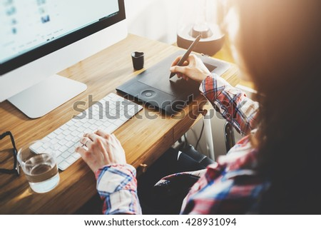 Young hipster graphic designer woman using digital graphic tablet while working at modern office, professional female retoucher sitting at modern workspace with wooden table, generic design tablet #428931094