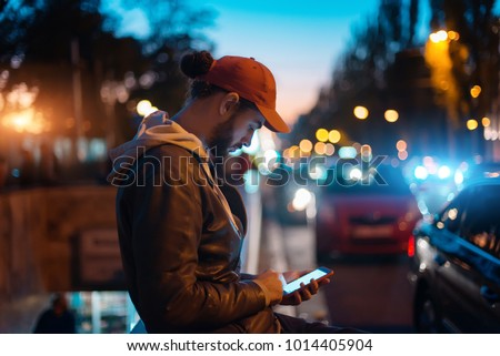 Young hipster guy using modern smartphone outdoors, man chatting with friends at social networks while walking at evening city streets
