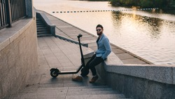 Young hipster man in a suit riding an electric scooter in bright sunny day. Ecological transportation concept.