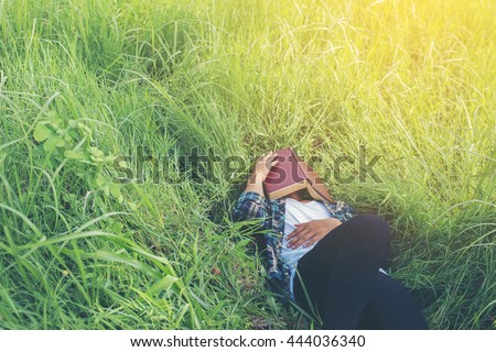 Young hipster man lying down on grassland napping tired after reading book with nature around.