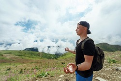 Young hipster Man meditates against the background of mountains in clouds