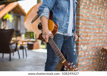 Young hipster man playing guitar to relaxing on his holiday, enjoy with natural and fresh air. #508249627