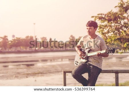 Young hipster man playing guitar to relaxing on his holiday, enjoy with natural and fresh air. #536399764