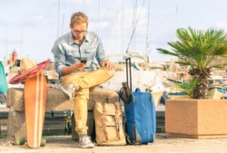 Young hipster man ready for the next destination vacation holding his smartphone. Modern concept of freedom and alternative lifestyle - Cheap travel backpacking around the world