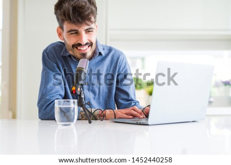 Young hipster man recording podcast using laptop, broadcasting an interview using microphone