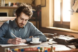 Young hipster man sketching on a notebook in his studio on a rustic wooden table