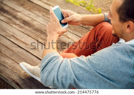 Young  hipster man using smart phone sitting on wooden boards stock photo