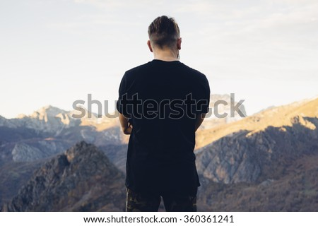 young hipster man wearing a black blank t-shirt on the mountain background. Back view
