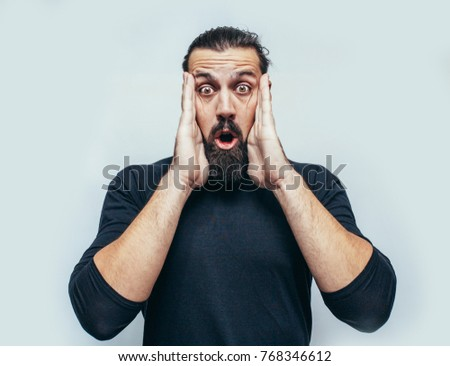 """Young hipster man wearing casual blue t-shirt staring at camera with shocked look, expressing astonishment and shock, screaming """"Omg"""" or """"Wow"""". disappointment. Crazy emotions. surprise. The emotional"""
