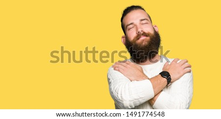 Young hipster man wearing winter sweater Hugging oneself happy and positive, smiling confident. Self love and self care