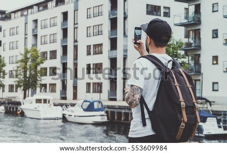 Young hipster man with backpack, taking pictures of street on smart phone at journey in Copenhagen, city tourism, cold colors