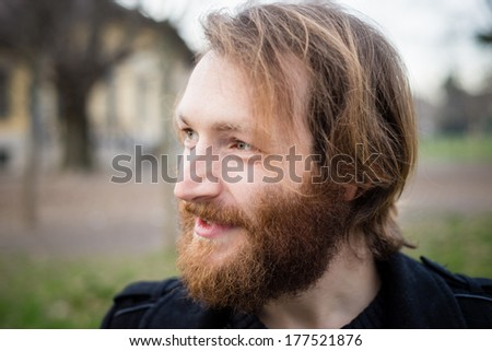 young hipster red bearded man at the park
