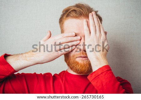 Young hipster red bearded Man closes his eyes with his hands