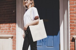 Young hipster smiling girl with white blank cotton shopper paper bag wearing white t-shirt and black jeans, mock-up of blank bag, brick wall and blue door on the background