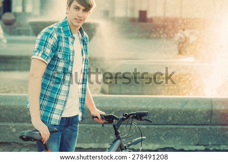Young hipster style man posing with bicycle on the street sport style picture handsome guy  ready for trip
