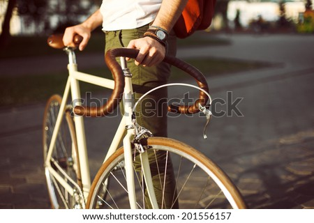 Young hipster style man posing with bicycle on the street sport style picture handsome guy with red backpack ready for trip