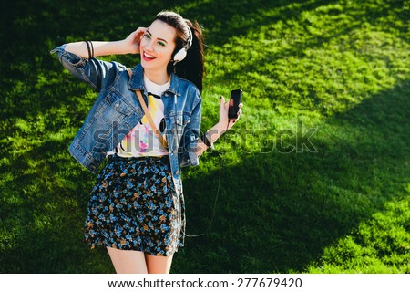 young hipster stylish beautiful girl listening to music, mobile phone,headphones, enjoying, denim outfit, smiling, happy, cool accessories, vintage style, having fun, laughing, park