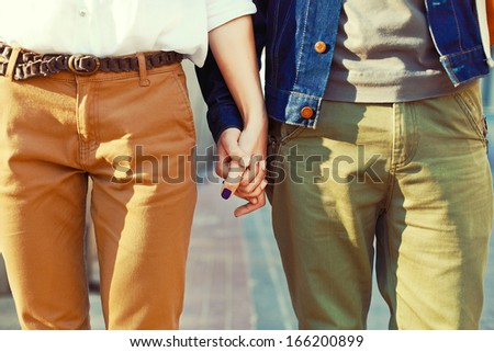 Young hipster stylish couple in love standing together Holding hands