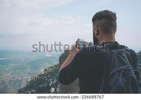 Young hipster taking picture with phone camera of landscape #326688767
