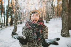 Young hipster woman in winter forest having fun with snow falling in hands