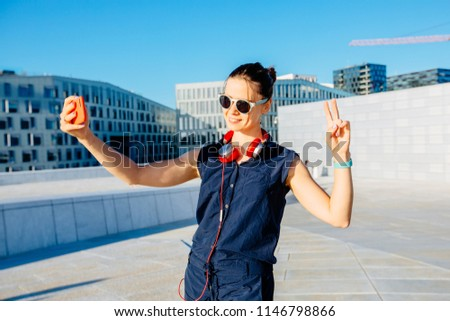 Young hipster woman traveler in sunglasses walking in Oslo city summer sunny day with red headphones, street style, modern norwegian urban background, happy, smiling. taking selfie photo.