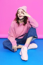 Young hipster woman wearing pink sweatshirt, hat, jeans and sneakers. Fashion studio shot