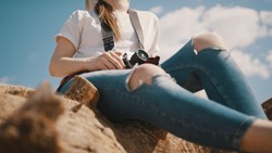 young hipster woman with vintage camera relaxing on the tree trunk. Freelance photographer enjoying a moment in nature