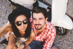 Young hipsters couple in love sitting near a scooter and posing outdoors in summer time wearing trendy clothes and sunglasses.