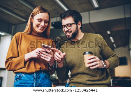 Young hipsters watching funny videos in social networks via mobile phone connected to wireless while bearded man holding cup of coffee, smiling girl checking notification at modern gadget indoors #1258426441