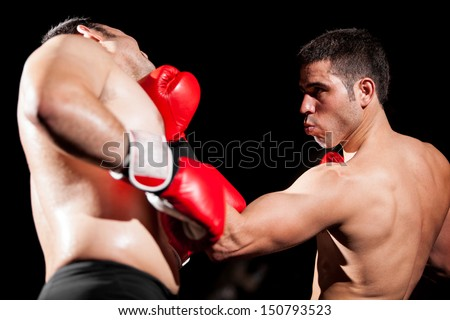 Young Hispanic boxer throwing an uppercut and hitting his opponent during a box fight
