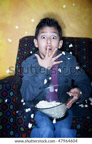 Young Hispanic boy with popcorn watching television