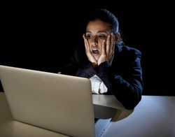 young hispanic business woman or student girl working in darkness on laptop computer late at night surprised in shock and angry in stress in crisis and failure concept isolated on black background