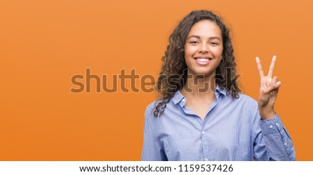 Young hispanic business woman showing and pointing up with fingers number two while smiling confident and happy. #1159537426