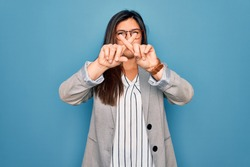 Young hispanic business woman wearing glasses standing over blue isolated background Rejection expression crossing fingers doing negative sign