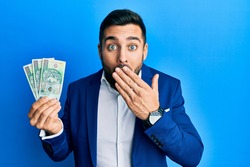 Young hispanic businessman wearing business suit holding polish zloty banknotes covering mouth with hand, shocked and afraid for mistake. surprised expression