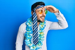 Young hispanic businessman wearing party funny style with tie on head very happy and smiling looking far away with hand over head. searching concept.