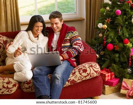 Young Hispanic couple Christmas shopping online