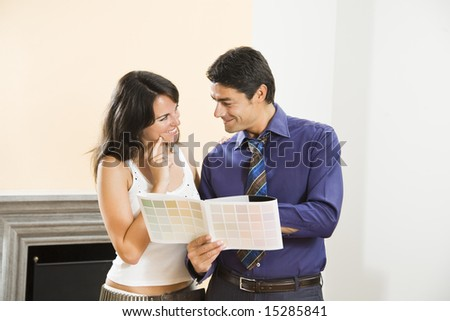 Young Hispanic couple looking at paint swatches for new home