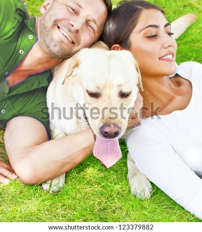 Young hispanic Couple lying with  white Dog